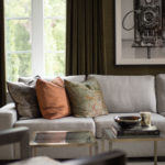 Image of modern living room detail featuring sofa with pillows.