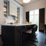 Image of modern kitchen featuring an custom marble island countertip and cabinetry.