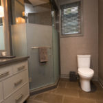 Photo of modern bathroom featuring glass shower, toilet, mirror and counter